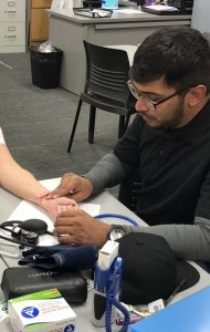 male student practicing vitals